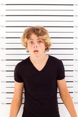 Shocked teen boy taking police mug shot — Stock Photo