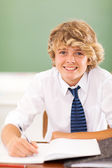Teenage boy writing in class — Stock Photo