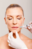 Mature woman receiving lips injection — Foto Stock