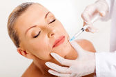 Middle aged woman receiving chin injection — Stock Photo