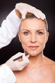 Doctor marking senior woman face — Stock Photo