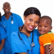 Stock Photo: Black pediatrician and baby boy with co-workers on background
