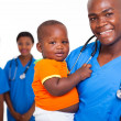 African american male pediatric doctor with little boy — ストック写真