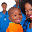 Young african nurse carrying baby boy — Stock Photo