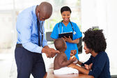 Pediatric doctor examining a child — Stockfoto