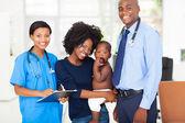 Professionisti medici pediatrici con madre tenendo il suo bambino — Foto Stock