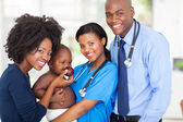 African pediatricians with mother and baby after checkup — Stock Photo