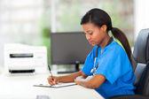 Infermiera pediatrica femmina scrivere relazioni mediche — Foto Stock