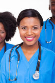 Female nurse with colleagues on background — Stock Photo