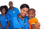 Black pediatrician and baby boy with co-workers on background — Photo