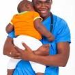 African american male pediatric doctor carrying a child — Stock Photo #23070056