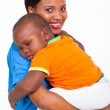 Portrait of young african nurse carrying sleeping baby boy — Stock Photo #23070080