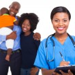 Female african american nurse with family patients — Stock Photo