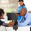 Stock Photo: African medical doctor monitoring patient's blood pressure