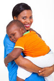 Portrait of young african nurse carrying sleeping baby boy — Stock Photo