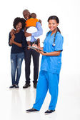 African american female nurse with family — Stock Photo