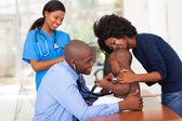 African mother and her son in doctor's office with doctor and nu — Stock Photo