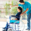 Caring husband and disabled wife looking outside window — Stock Photo #23775079