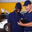 Happy auto mechanics going through checklist — Stockfoto