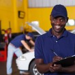 African american male vehicle mechanic writing report — Stock Photo #24226535