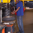 Tyre shop worker inflating a trye - 图库照片
