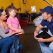 Friendly auto technician talking to customer's daughter — Stock Photo