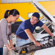 Mechanic showing customer car problem - Stock Photo