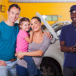 Happy family in garage with auto mechanic — Stock Photo #24229207