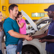 Friendly mechanic handshaking with family — Stock Photo