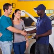 Auto technician handshaking with couple — Stock Photo