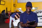 Afroamerikaner männlich fahrzeug-mechaniker bericht schreiben — Stockfoto