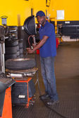 Tyre shop worker inflating a trye — Stock Photo