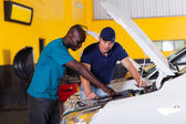 African man showing auto mechanic car problem — Stock Photo
