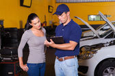 Auto mechanic and young woman in workshop — Stock Photo