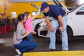 Cute little girl palying with auto mechanic — Stock Photo