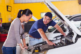Mechanic showing customer car problem — Stock Photo