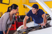 Auto technician talking to customer — Stockfoto