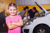 Cute little girl waiting for mother in garage — Stock Photo