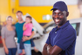 Trustworthy auto mechanic in front family — Stock Photo