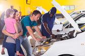 молодая семья, принимая их автомобиль для ремонта — Стоковое фото