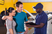 Auto mechanic talking to young couple — Stock Photo