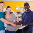 Young couple giving thumb up to auto repair shop — Stock Photo