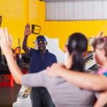 Friendly auto repair shop worker waving good bye to customer — Stock Photo