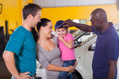 Friendly auto mechanic playing with little girl — Stock Photo