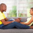 Young african couple sitting on the couch — Stock Photo #24412833