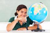 Teenage school girl pointing the globe — Stock Photo