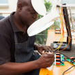 Senior african technician repairing circuit board - Stock Photo