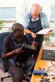 Two senior men assembly electronic equipment in workshop — Stock Photo