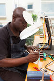 Senior african technician repairing circuit board — Stock Photo