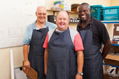 Senior small business owner and employees — Stock Photo